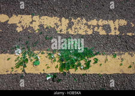 Broken green glass lying in a pile on double-yellow lines in a south London gutter. - Stock Photo