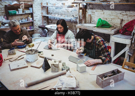 Men and woman working at workshop - Stock Photo