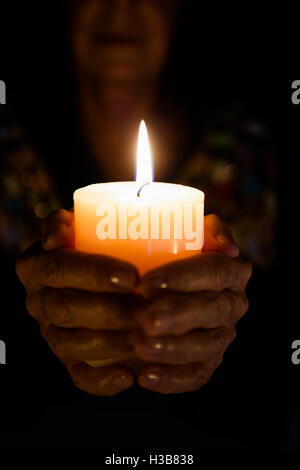 Cropped image of female fortune teller holding lit candle - Stock Photo