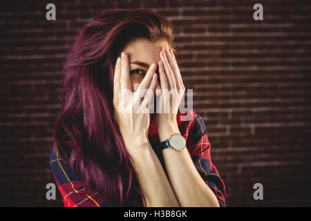 Young woman hiding face behind hands - Stock Photo