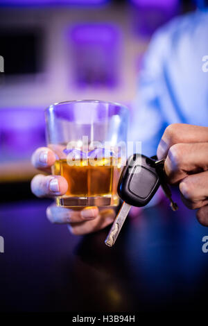 Man holding a glass of whiskey and car keys