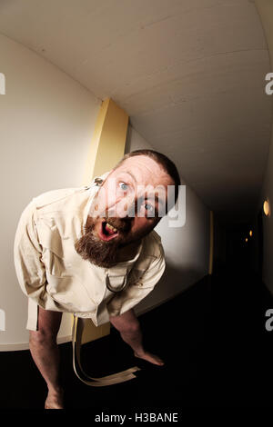 Photo of an insane man in his forties wearing a straitjacket standing in the hallway of an asylum.  Taken with a - Stock Photo