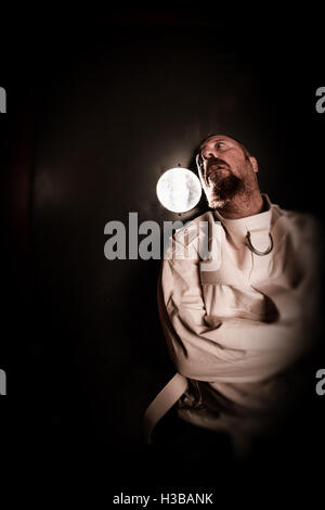 Photo of an insane man in his forties wearing a straitjacket standing in a cell of an asylum with the light from - Stock Photo