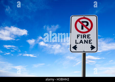 A Fire Lane No Parking sign against a blue cloudy sky with copy space. Horizontal orientation. - Stock Photo