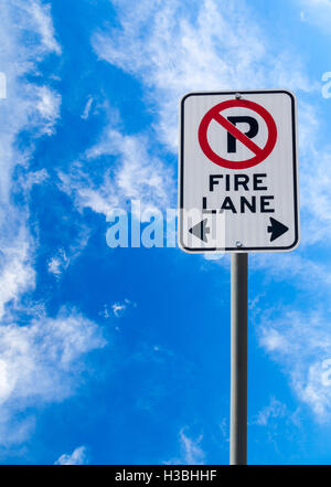 A Fire Lane No Parking sign against a blue cloudy sky with copy space. Vertical orientation. - Stock Photo