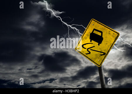 Slippery when wet road sign against a stormy background with lightning and copy space. Dirty and angled sign adds - Stock Photo