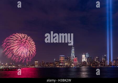 September 11 Tribute in Light and fireworks near freedom Tower in Manhattan New York - Stock Photo