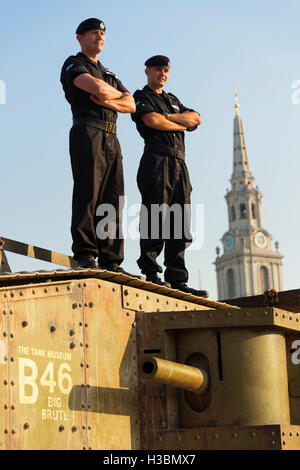 Two soldiers from the Royal Tank Regiment standing on a replica Mk IV World War One tank in Trafalgar Square, London. - Stock Photo