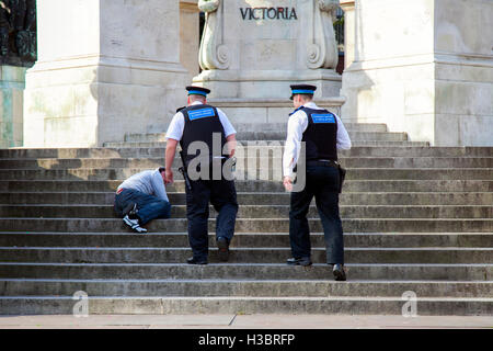 Homelessness and Rough Sleepers in the city Centre. Police Community Officers investigate homeless sleeping man - Stock Photo