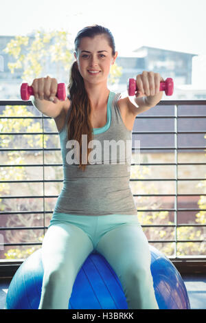 Portrait of woman holding dumbbell while sitting on exercise ball - Stock Photo