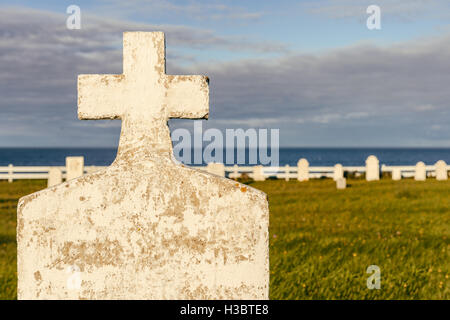 Blank headstone in a cemetery, with ocean in the background, at sunset - Stock Photo