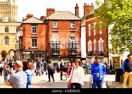 People enjoying a sunny day in the old part of the city center in Lincoln, England - Stock Photo
