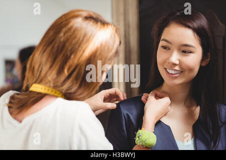 Fashion designer measuring woman's shoulders - Stock Photo