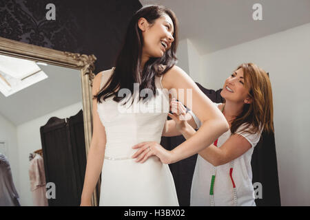 Woman trying on wedding dress with the assistance of creative designer - Stock Photo