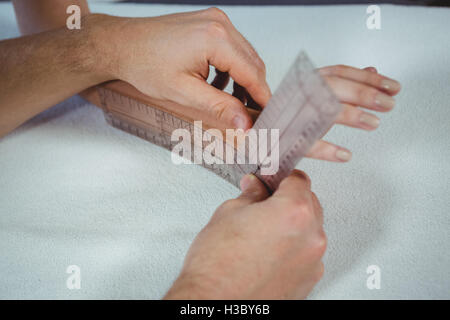Physiotherapist examining female patient's wrist with goniometer - Stock Photo