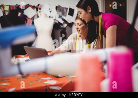 Female fashion designer working on a laptop - Stock Photo