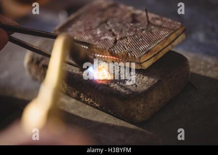 Goldsmith crafting ring by burner - Stock Photo