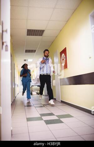 Doctor and nurse running in hospital corridor - Stock Photo