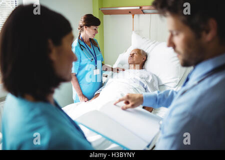 Nurse consoling senior patient - Stock Photo