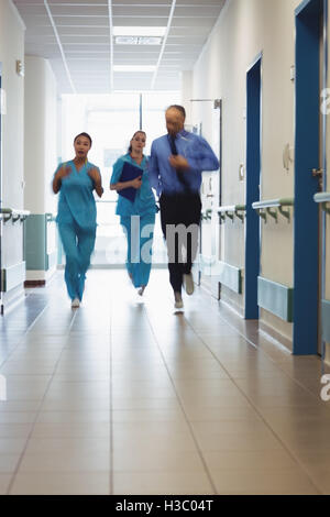 Doctor and nurse running in passageway of hospital - Stock Photo