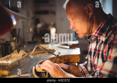 Goldsmith shaping metal with coping saw - Stock Photo