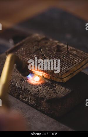 Goldsmith welding stone by burner - Stock Photo