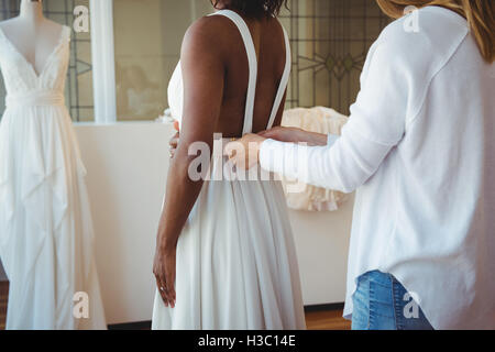 Woman trying on wedding dress with the assistance of fashion designer - Stock Photo