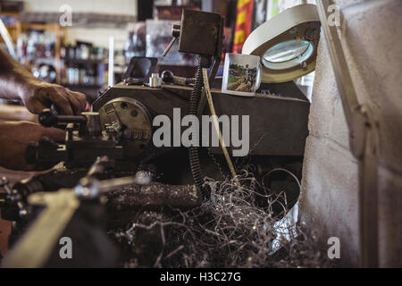 Mechanic working on a lathe machine - Stock Photo