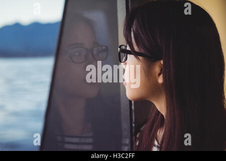Young woman looking through window - Stock Photo