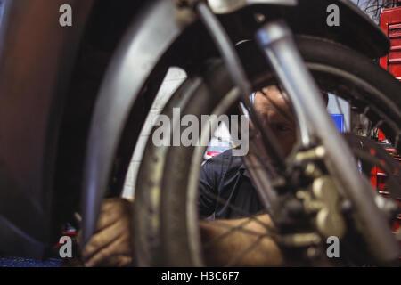 Mechanic examining a motorbike - Stock Photo