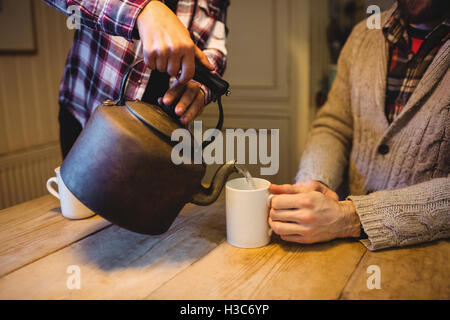 Mid-section of woman pouring water with a teapot - Stock Photo