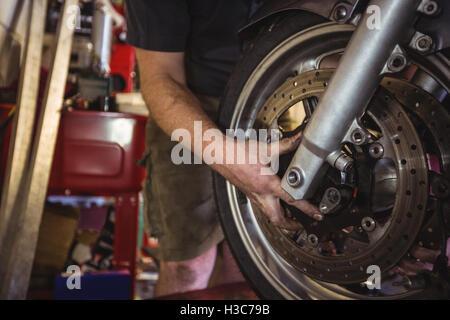 Mechanic examining a motorbike disc brake - Stock Photo