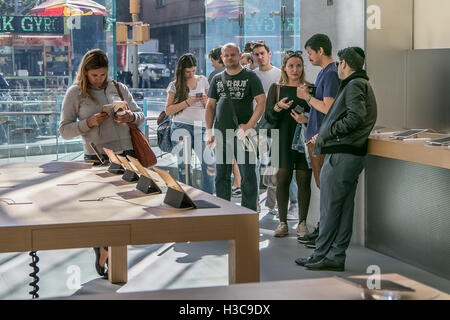 People stand in line in the Apple store on Manhattan's Upper West Side waiting to purchase a new iPhone. - Stock Photo