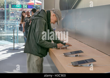 An elderly man is looking at an iPad tablet in the Apple store on Manhattan's Upper West Side. - Stock Photo