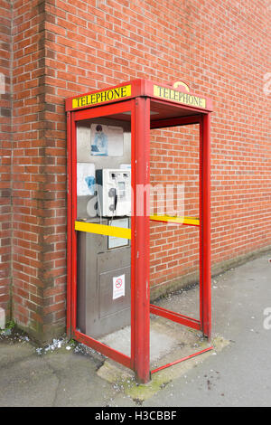 Modern utilitarian urban UK telephone kiosk is poor state due to vandalism. All glass panels have been broken and - Stock Photo