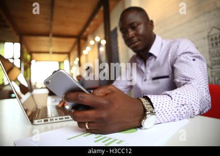 Black professional businessman in business formal attire on mobile cell smartphone - Stock Photo