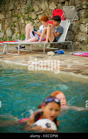 Boy Sitting Next To Swimming Pool Reading Book High Angle View Stock Photo Royalty Free Image