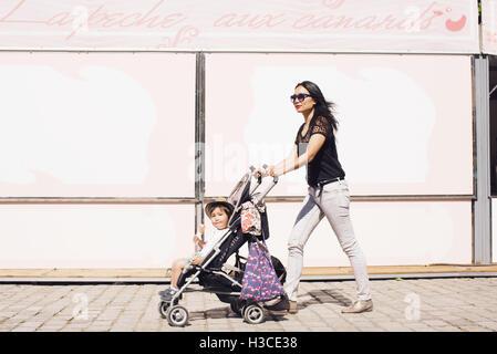 Mother pushing toddler son in stroller on sidewalk - Stock Photo