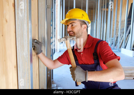 Carpenter using hammer in a construction site - Stock Photo
