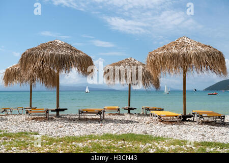 Tropical thatch umbrellas and lounges on a beach in a sunny weather in Greece. - Stock Photo