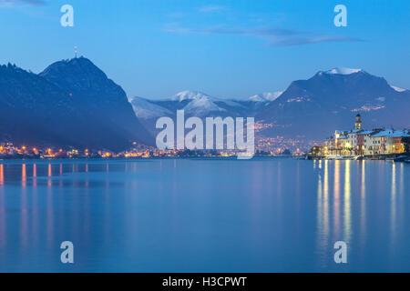 Blue hour in Brusino Arsizio and Lugano in the distance, Lake Ceresio, Canton Ticino, Switzerland. - Stock Photo