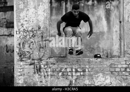 A Colombian parkour runner performs a jump over an obstacle during a training of Plus Parkour team in Bogotá, Colombia. - Stock Photo