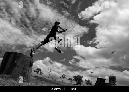 A Colombian parkour athlete performs a high jump during a free running training session in a park in Bogotá, Colombia. - Stock Photo