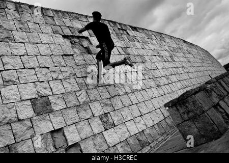 A Colombian parkour runner jumps on the wall during a free running training session in a park in Bogotá, Colombia. - Stock Photo