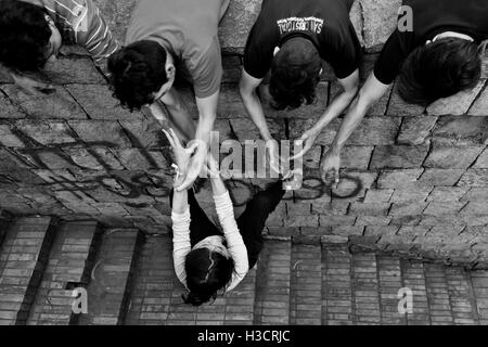 A Colombian female freerunner, hung on his mates' hands, climbs on the wall during a parkour training in Bogotá, - Stock Photo