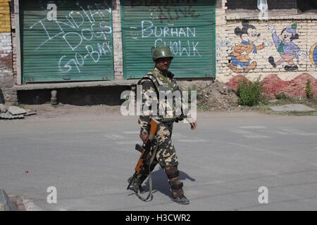 Srinagar, India. 06th Oct, 2016. Indian paramilitary trooper walking on road near the anti-India graffiti written - Stock Photo