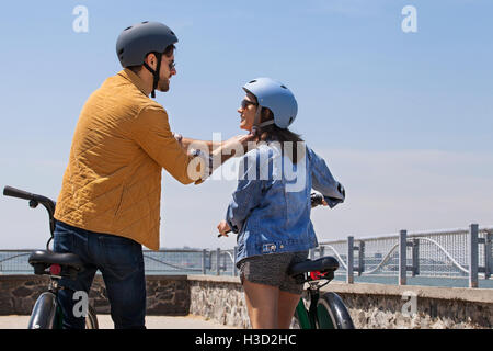 Rear view of man assisting woman in wearing bicycle helmet on promenade - Stock Photo