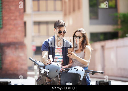 Young couple using smart phone while standing with Citi Bikes - Stock Photo
