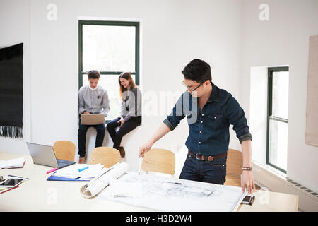 Businessman analyzing blueprints while colleagues using laptop in background - Stock Photo