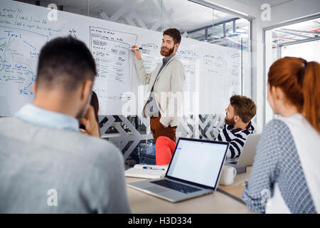 Businessman giving presentation to colleagues in board room - Stock Photo